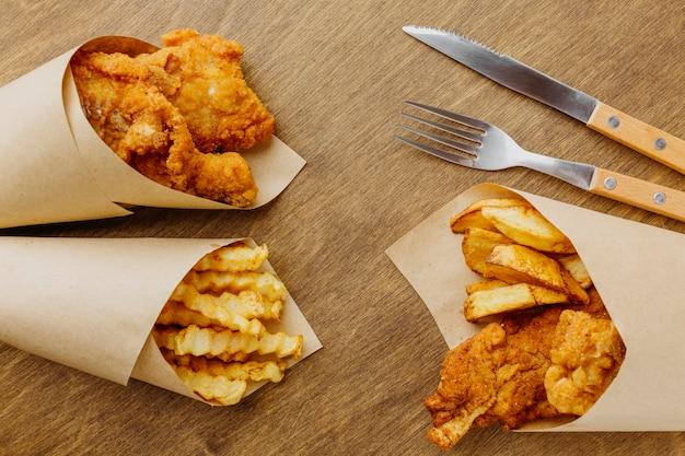 Вид сверху на рыбу с жареным картофелем в бумажной упаковке со столовыми приборами