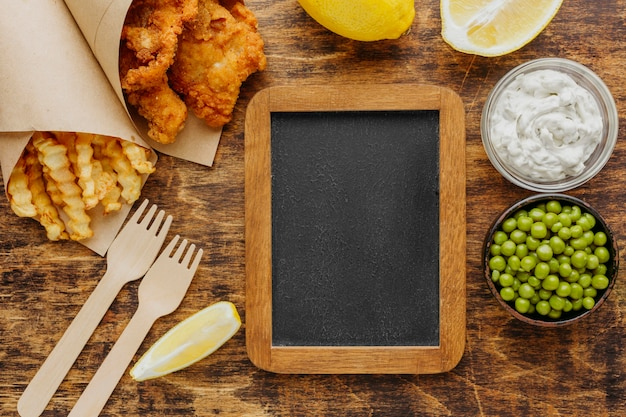 Вид сверху на рыбу с жареным картофелем в бумажной упаковке с горохом и классной доской