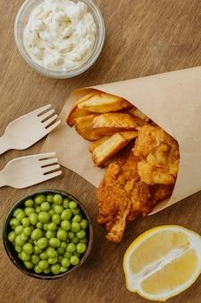 Вид сверху на рыбу с жареным картофелем в бумажной упаковке с горошком и соусом