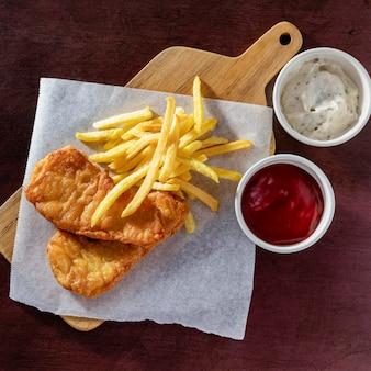 Вид сверху рыбы с жареным картофелем на разделочной доске