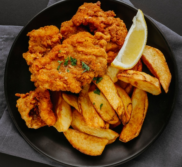 Вид сверху рыбы и жареного картофеля на тарелке с ломтиком лимона