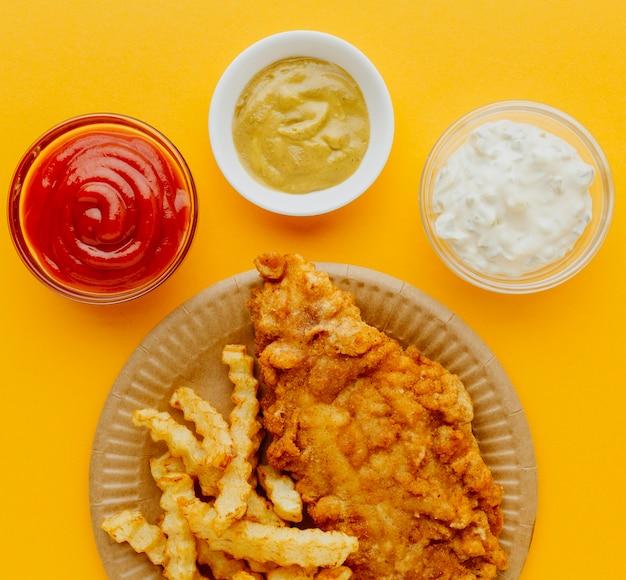 Вид сверху на рыбу с жареным картофелем на тарелке с соусами