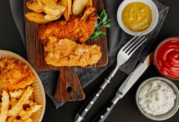 Вид сверху на рыбу с жареным картофелем с ассортиментом соусов