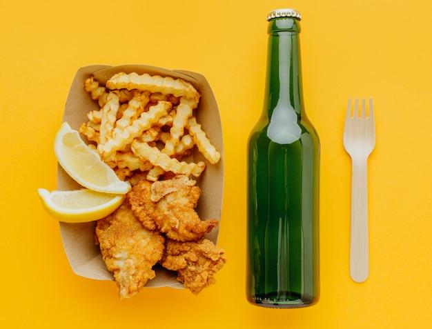 Вид сверху рыбы и жареного картофеля с пивной бутылкой и вилкой