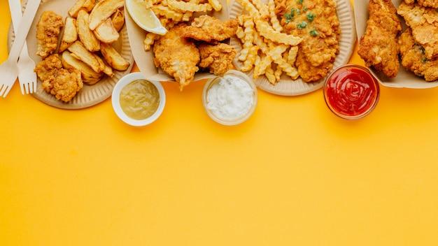 Вид сверху рыбы с жареным картофелем с копией пространства и разнообразных соусов