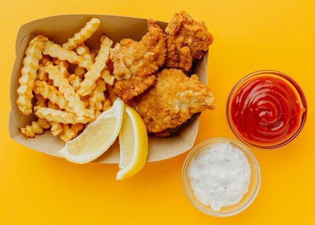 Вид сверху на рыбу и чипсы с кетчупом и соусом