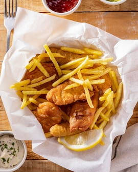 Вид сверху на рыбу с жареным картофелем с соусом из кетчупа