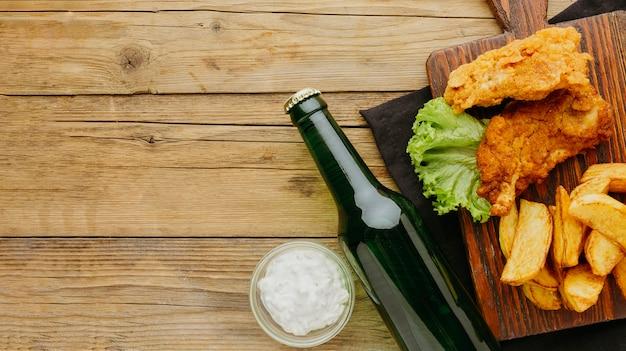 Вид сверху на рыбу и жареный картофель с соусом и пивной бутылкой