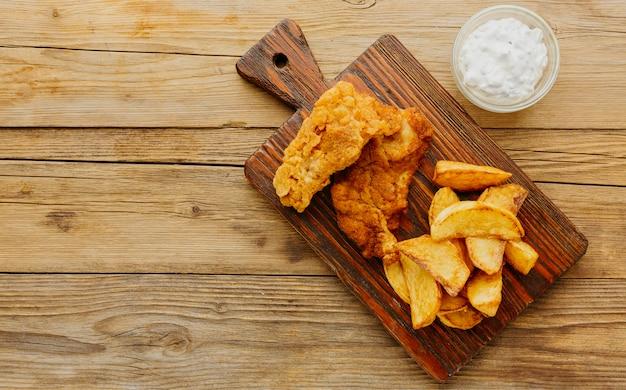 Вид сверху рыбы с жареным картофелем с соусом на разделочной доске