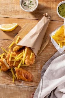 Вид сверху на рыбу с жареным картофелем с соусами