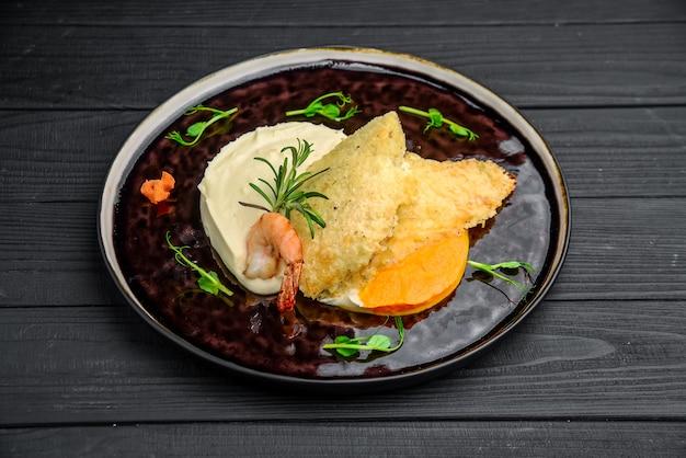 Вид сверху рыбного филе в масле с картофельным пюре на деревянном столе, домашняя кухня