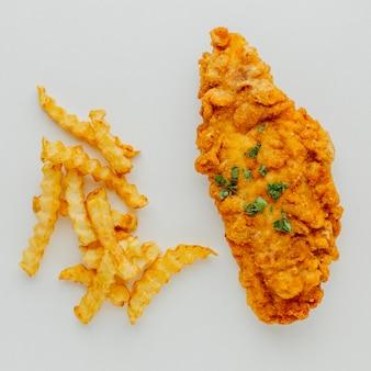 Вид сверху кусок рыбы и чипсы