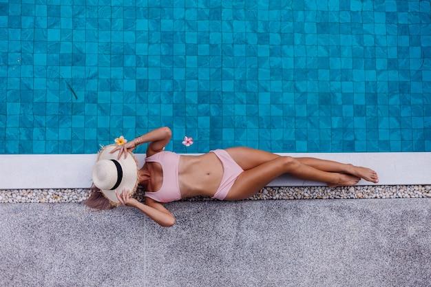 휴가를 즐기는 수영장의 가장자리에 비키니 입은 슬림 한 여자의 상위 뷰