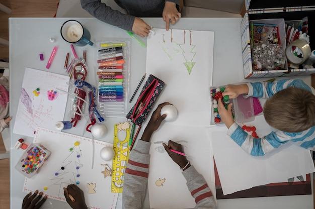 Вид сверху на пятерых детей, которые рисуют и создают украшения с блестками и различными красочными материалами.
