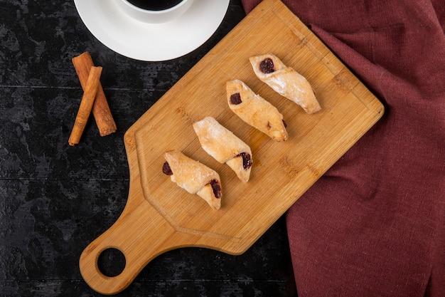 黒い背景に一杯のコーヒーとシナモンスティックで木の板にいちごジャムと小麦粉のクッキーのトップビュー