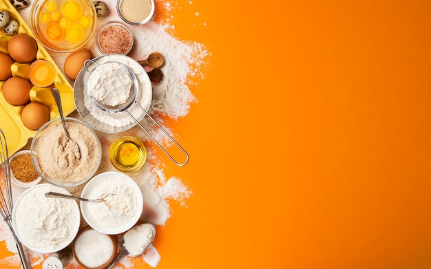 Вид сверху муки, яиц, масла, сахара и кухонной утвари на оранжевом фоне