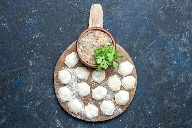 Вид сверху посыпанных мукой кусков теста с фаршем и зеленью на темном, тесто пищевое сырое мясо обеденное печенье