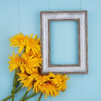 Вид сверху на цветы и рамка на синем с копией пространства