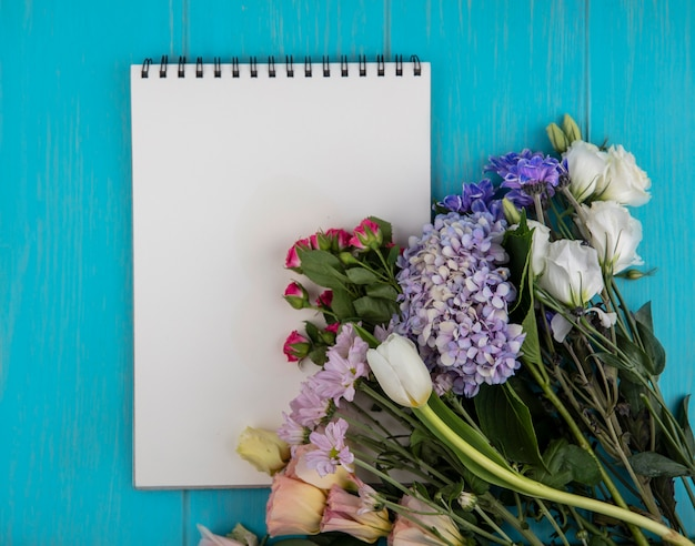 コピースペースと青い背景に花とメモ帳の上面図