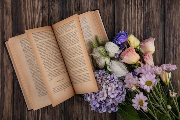 花の上面図と木製の背景に開いた本