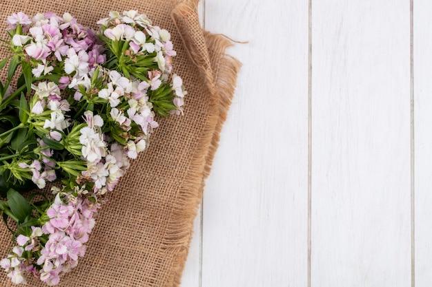 Вид сверху цветов на бежевой салфетке белой поверхности