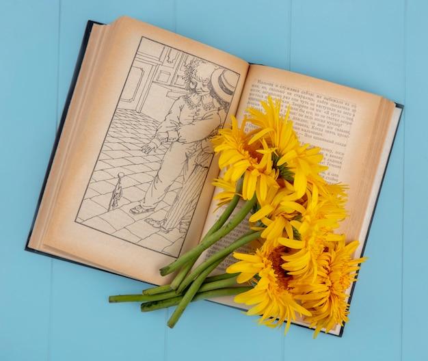 Вид сверху цветов на открытой книге на синем