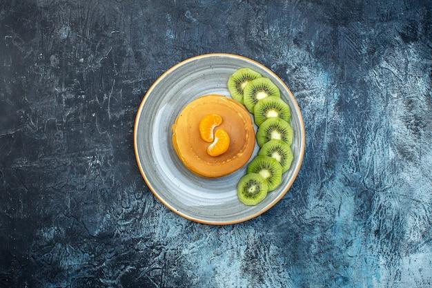Вид сверху на пушистые блины в американском стиле из натурального йогурта, поданные с киви на тарелке на фоне льда