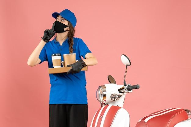 パステル ピーチ色の背景にコーヒーの小さなケーキを保持しているオートバイの隣に立っている医療マスク手袋を着た宅配便の女の子のトップ ビュー