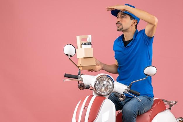 파스텔 복숭아 배경에 스쿠터 지주 주문에 앉아 모자를 쓰고 의료 마스크에 집중된 택배 남자의 상위 뷰