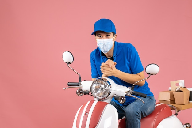 パステル調の桃の背景にスクーターに座っている帽子をかぶった医療マスクを着た宅配便の男性のトップビュー