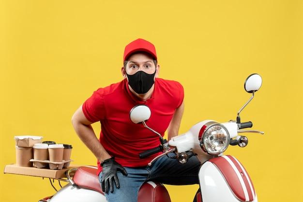 黄色の背景のスクーターに座って注文を配信医療マスクで赤いブラウスと帽子の手袋を身に着けている焦点を当てた若い大人の上面図