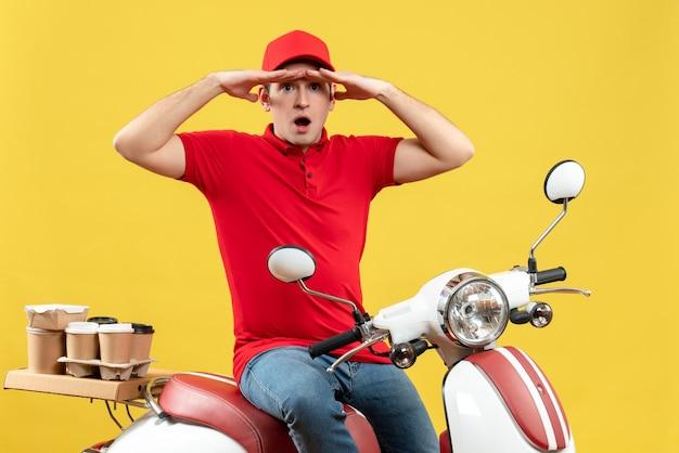 黄色の背景に注文を配信する赤いブラウスと帽子を身に着けている焦点を当てた若い男の上面図
