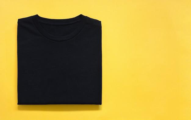 Вид сверху сложенной футболки черного цвета