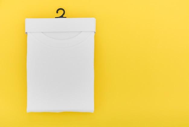 Вид сверху на сложенную белую футболку в бумажной подвесной упаковке на желтом фоне