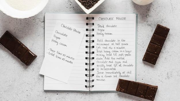 Вид сверху пищевых ингредиентов с шоколадом и рецептом