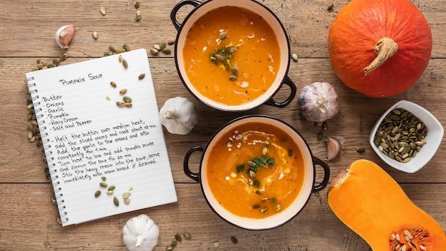 Вид сверху пищевых ингредиентов с тыквенным супом и блокнотом
