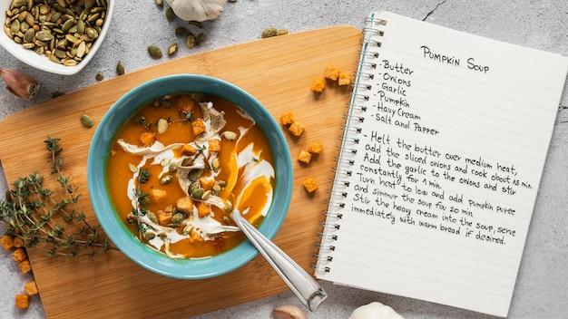Вид сверху пищевых ингредиентов с миской овощного супа и ноутбуком