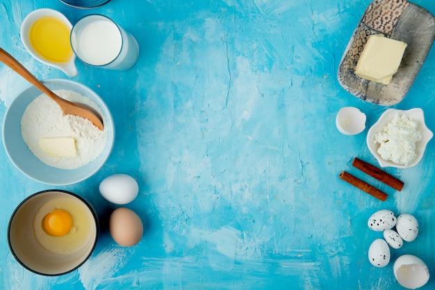 Вид сверху продуктов, как мука, масло, молоко, творог, корица и яйцо на синем фоне с копией пространства