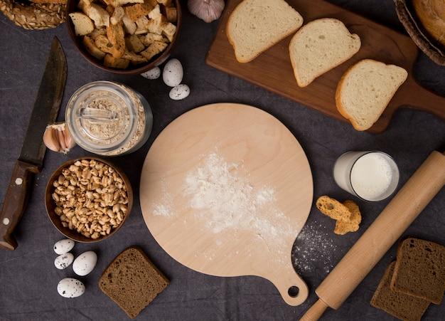 Вид сверху продуктов, как мука, овсяные хлопья, мозоли, яйца с хлебом, нож, разделочная доска, молоко на бордовом фоне
