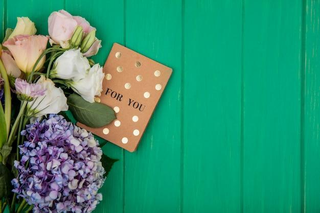 コピースペースのある緑の背景にカードと花の上面図