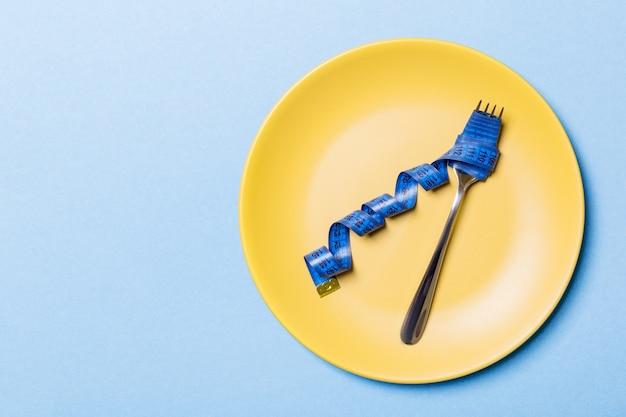 Вид сверху вилки с рулеткой в круглой пластине на синем фоне. концепция потери веса с пустым пространством для вашей идеи.