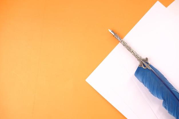Вид сверху перьевой ручки на оранжевом фоне.