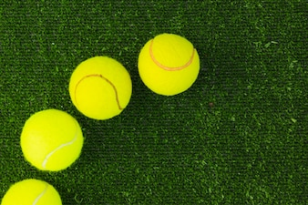 Top view of four racket balls on green turf