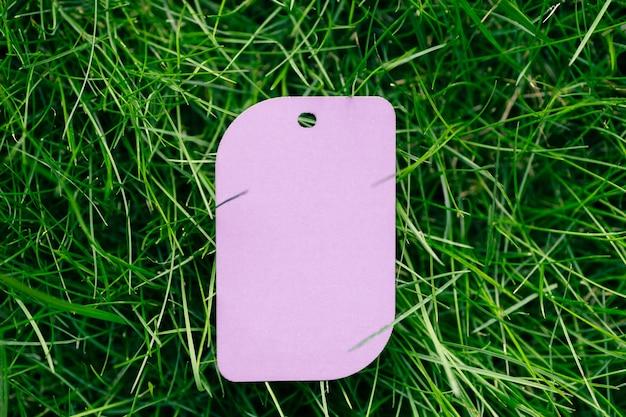 緑の春の草で作られたフレームの上面図とロゴのコピースペースで販売されている葉の形のラベルのない1つのラベル。自然な概念。