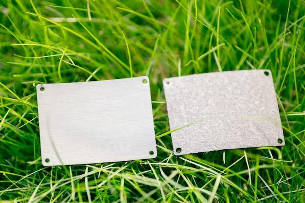 緑の春の草とロゴのコピースペースで販売されている2つの灰色の革パッチで作られたフレームの上面図。自然な概念。