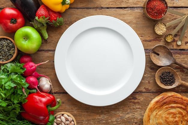Взгляд сверху продуктов рамки различных, трав, восточных специй, белой плиты с космосом для текста на постаретой деревянной предпосылке, горизонтального, расположения, космоса экземпляра, концепции здорового питания, модель-макета