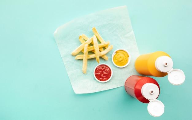 컬러 테이블 배경에 토마토 소스 (케첩)와 겨자 병으로 튀긴 프랑스의 상위 뷰 패스트 푸드 및 건강에 해로운 식사 개념 아이디어