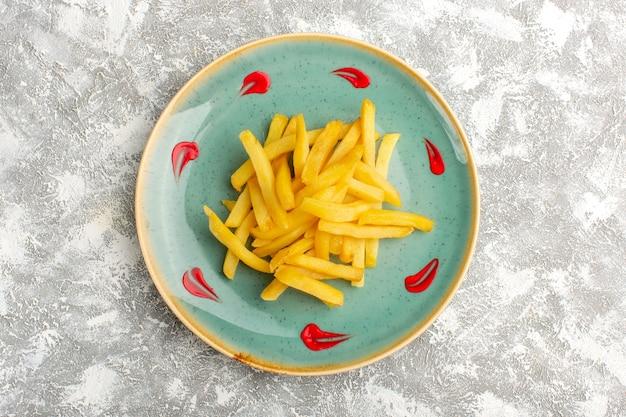 Вид сверху картофеля фри, приготовленного и соленого внутри тарелки на светлой поверхности
