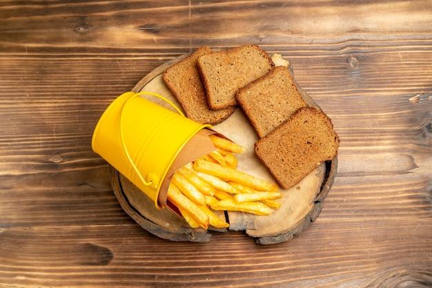 갈색 테이블에 어두운 빵과 감자 튀김의 상위 뷰