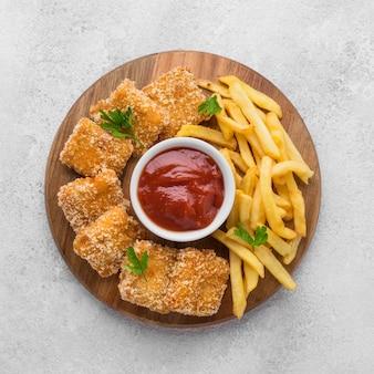 Вид сверху на картофель фри с жареными куриными наггетсами и соусом